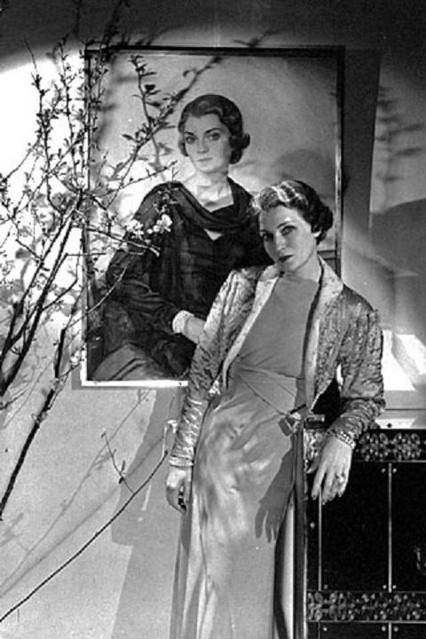Mrs. Harrison Williams, later Mona, the Countess of Bismarck, in front of her portrait by Sorin. Photo by Cecil Beaton. Vogue, October 1, 1933.