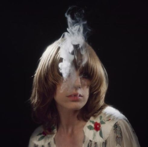 Singer Marianne Faithfull blows smoke from her mouth as she poses in a dress by Ossie Clark in 1973.